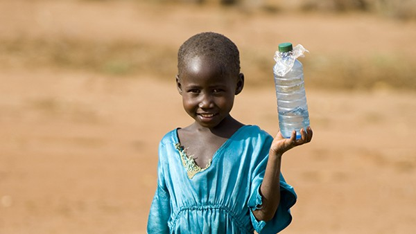 young child transporting an old plastic bottle full of water