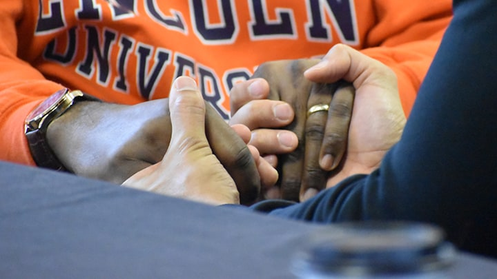 Two people hold hands to pray