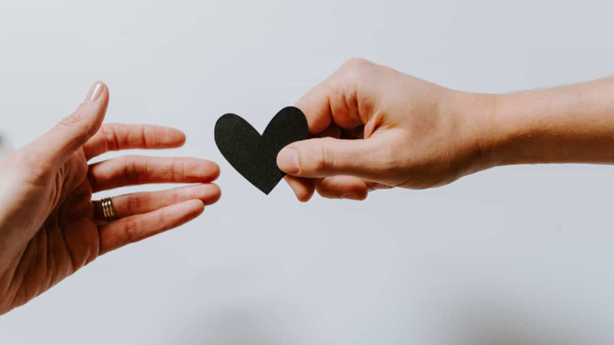 One Hand Giving A Paper Heart To Another Hand